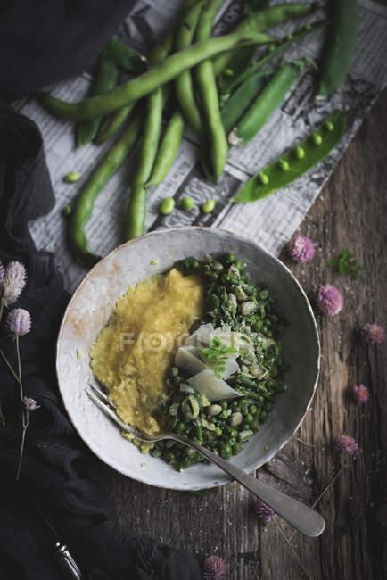 Direttamente sopra la piastra con polenta e piselli sulla tavola rustica — Foto stock