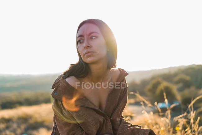 Брюнетка Чуттєва жінка, сидячи в природі і дивиться в бік — стокове фото