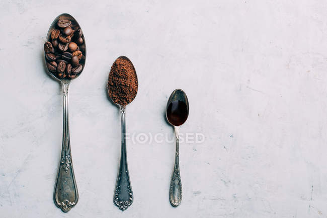 Row of spoons with coffee beans, ground coffee on wihite background — Stock Photo