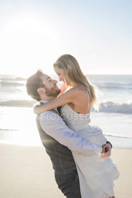 Прекрасная супружеская пара, обнимающаяся на солнечном пляже — стоковое фото