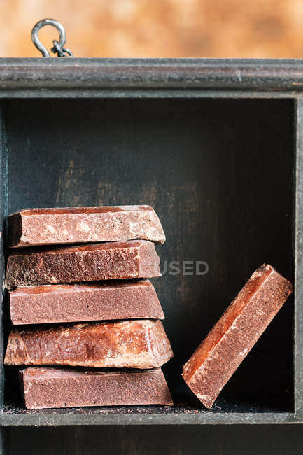 Close up view of stacked chocolate bars in wooden box — Stock Photo