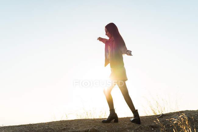 Вид сбоку на молодую женщину, идущую по холму на фоне закатного неба — стоковое фото