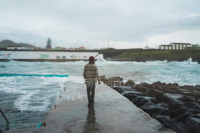 Задній вид людини при ходьбі на пристані на березі моря на скелястому узбережжі. — стокове фото