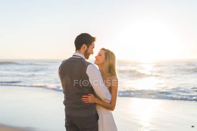 Tender bridal couple looking at each other at beach in sunlight — Stock Photo