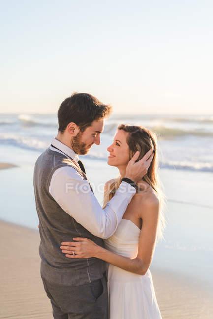 Нежная супружеская пара, позирующая на пляже в солнечном свете — стоковое фото