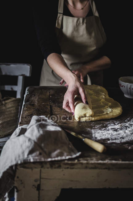 Femme de culture rouler la pâte pendant la cuisson de la pâte sucrée sur la table de la cuisine. — Photo de stock