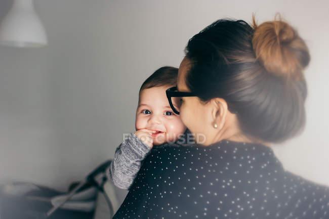Adorable chico en la madre manos mirando a la cámara - foto de stock