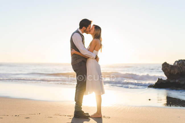 Backlit bridal couple kissing on beach in sunlight — Stock Photo