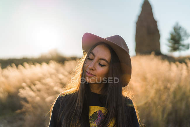 Cheerful brunette woman in hat posing in nature with closed eyes — Stock Photo