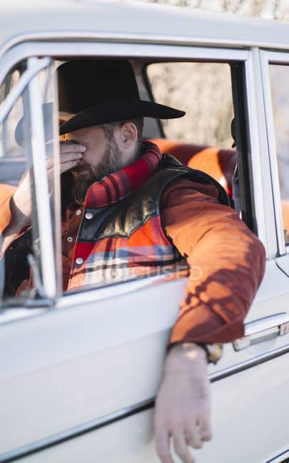 Cansado homem maduro no chapéu sentado no carro e esfregando os olhos — Fotografia de Stock