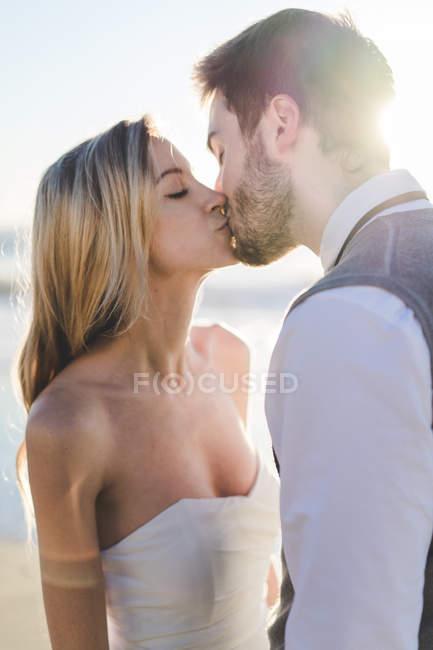 Нежные поцелуи невесты в лучах солнца — стоковое фото