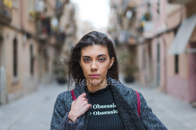 Young brunette woman looking at camera on city street. — Stock Photo