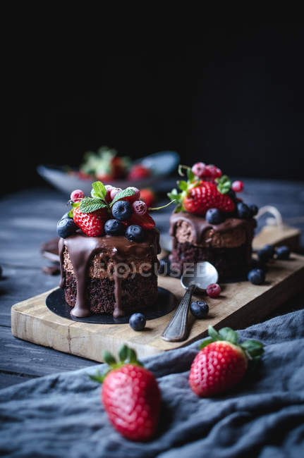 Tasty sweet chocolate cakes decorated with different berries on wooden table. — Stock Photo