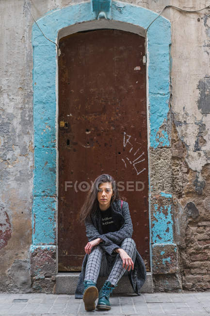 Young woman sitting on grungy doorstep and looking at camera — Stock Photo