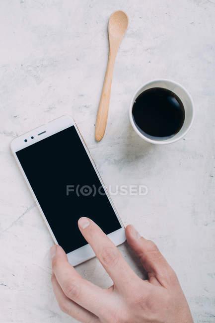 Кадрирование мужской руки касаясь экрана смартфона на столе с кофе — стоковое фото