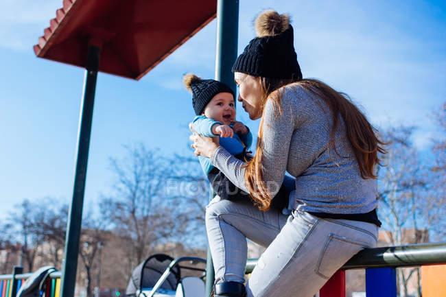 Mère joyeuse assise et jouant avec le fils tout-petit sur l'aire de jeux . — Photo de stock