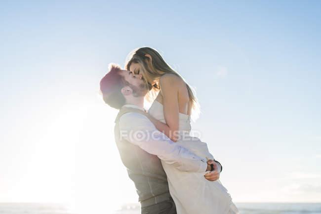 Свадебная пара обнимается и целуется на пляже — стоковое фото