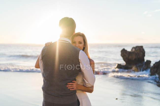 Zartes Brautpaar tanzt im Sonnenlicht am Meeresufer — Stockfoto