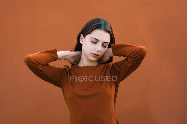Beautiful brunette in brown posing with closed eyes against brown background — Stock Photo