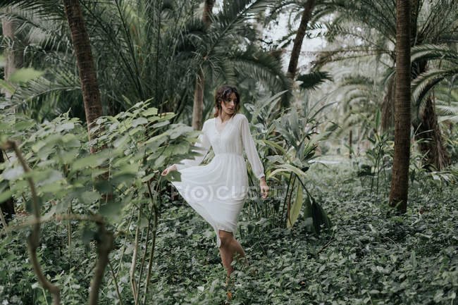 Романтическая девушка в белом платье прогулка в зеленом саду — стоковое фото