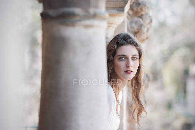 Pretty young woman in white dress posing at columns and looking at camera — Stock Photo
