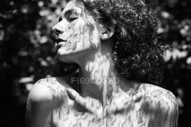 Чувственная девушка позирует с закрытыми глазами в тени кружева — стоковое фото