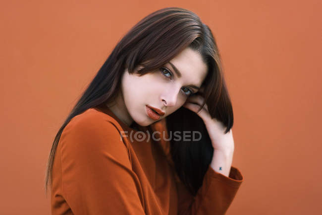 Emotionless girl in brown outfit touching face and looking at camera. — Stock Photo