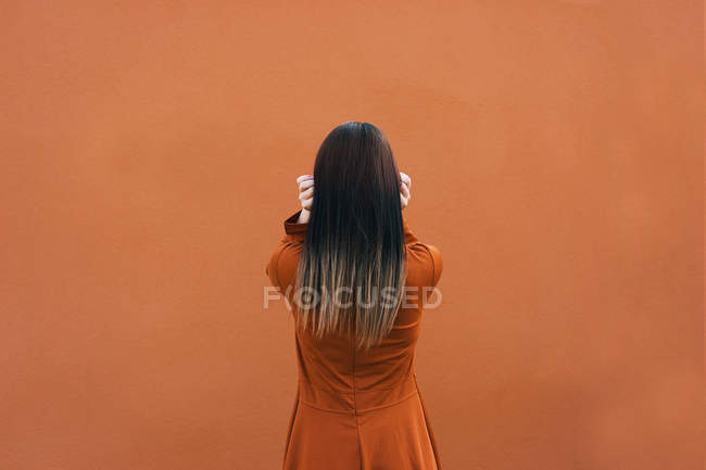 Rear view of brunette in brown against brown background — Stock Photo