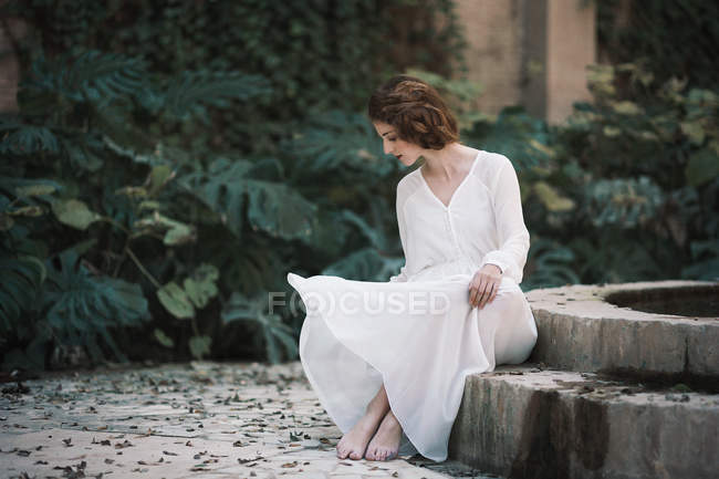 Brunette woman in white dress sitting at pond in park — Stock Photo