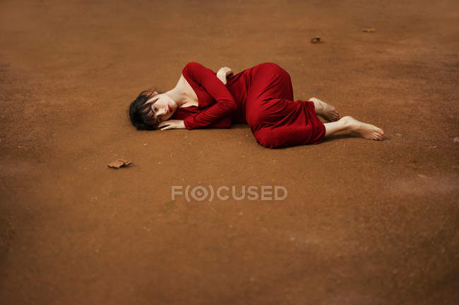 Brunette girl lying barefoot on brown ground crouched. — Stock Photo
