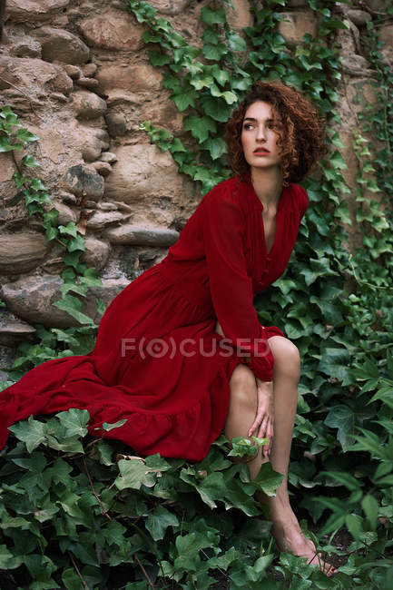 Sensual young girl  in red dress sitting on ivy embraced cliffs — Stock Photo