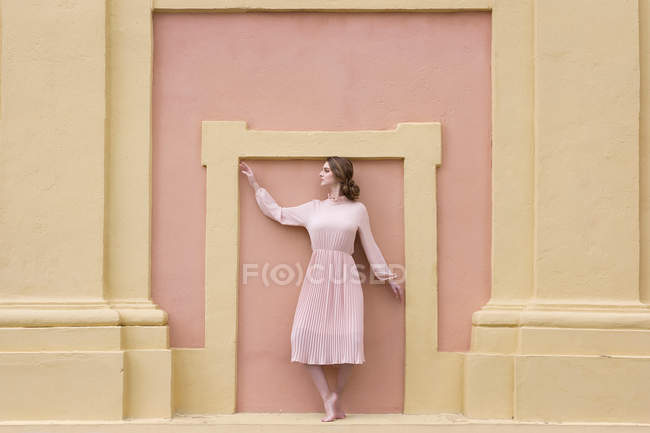 Pretty young woman in pink dress posing at pink facade — Stock Photo