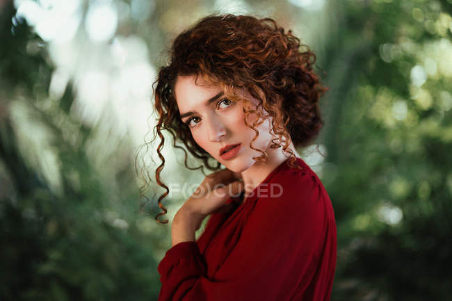 Curly woman in red dress and posing sensually on green. — Stock Photo