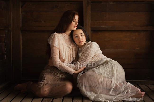 Jeunes filles porter des vieux vêtements élégants et assis dans une étreinte tendre sur bois — Photo de stock