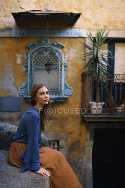 Serene woman sitting on ledge and looking at camera — Stock Photo