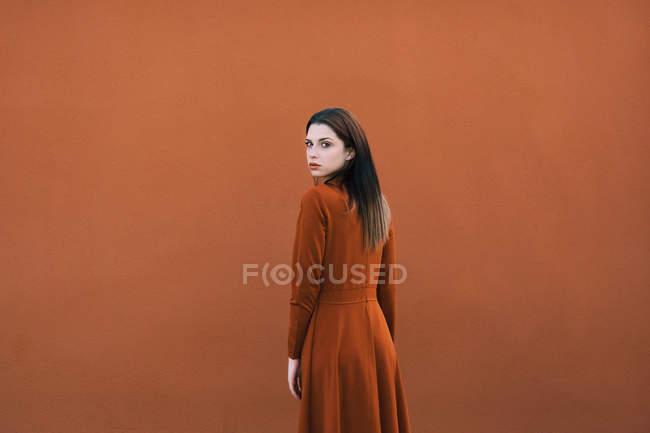 Брюнетка в коричневый глядя через плечо на камеры вид сзади — стоковое фото