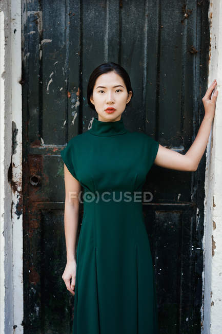 Asian woman posing in shabby doorway — Stock Photo