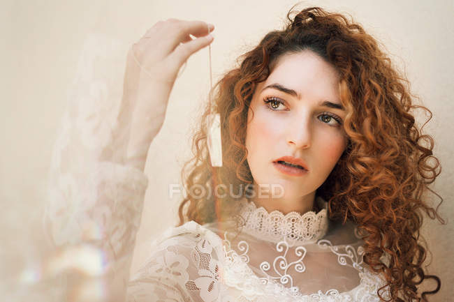 Curly  woman in white lace dress holding small crystal on chain — Stock Photo