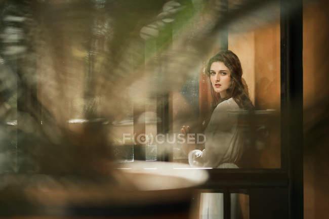 Брюнетка женщина, стоя в дверях и, глядя через плечо на камеру — стоковое фото