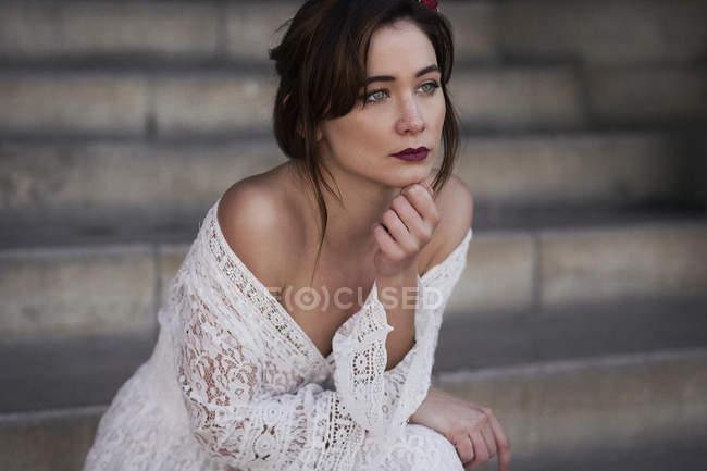Joven morena sensual en vestido de encaje blanco sentada en escalones y mirando hacia otro lado . - foto de stock