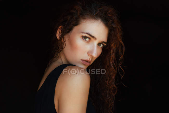 Alluring curly girl looking over shoulder at camera — Stock Photo