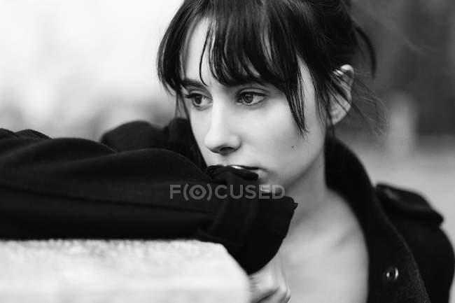 Mujer melancólica en negro apoyándose en la cerca - foto de stock