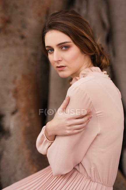 Brunette woman in pink vintage dress looking at camera — Stock Photo