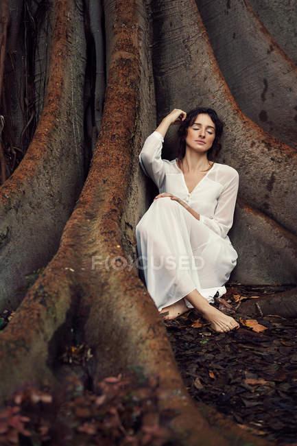 Träumen Brünette im weißen Kleid sitzt barfuß in den Wurzeln der alten Baum mit Augen geschlossen. — Stockfoto