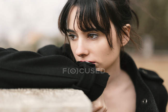 Melancholic woman in black leaning on fence and looking away — Stock Photo
