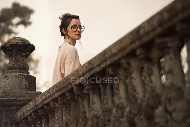 Мечтательная женщина на террасе, глядя через плечо прочь — стоковое фото