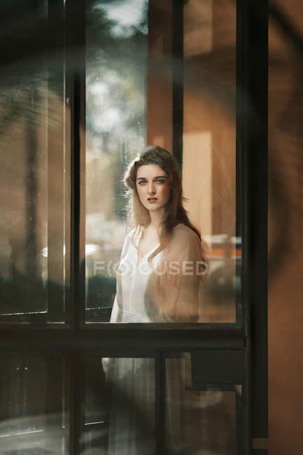 Jolie femme en robe blanche posant dans la porte et regarder la caméra — Photo de stock