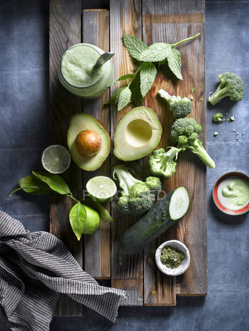 Puesta plana de brócoli fresco con pepinos y hierbas de aguacate sobre tabla de madera . - foto de stock