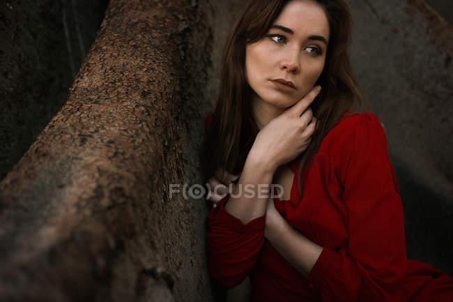 Morena sensual vistiendo vestido rojo y sentada por las raíces - foto de stock