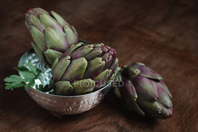 Still life of artichokes on wooden table — Stock Photo